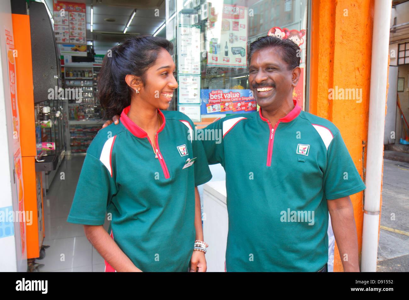 Singapore Singapore River Boat Quay uomo asiatico padre donna figlia adulta 7-Eleven convenience store uniforme Immagini Stock