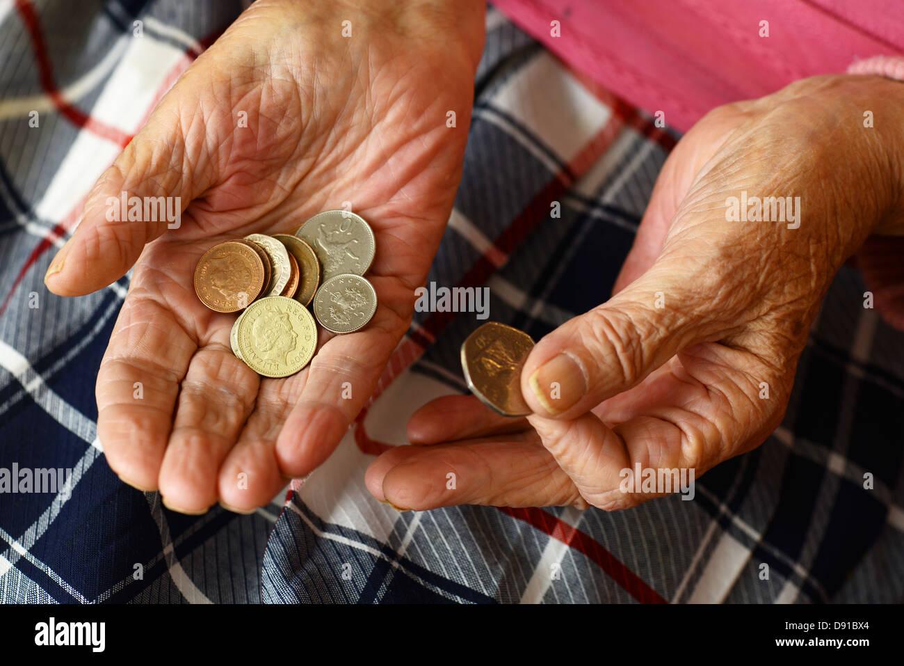 Soldi, monete in una donna anziana con le mani in mano, close up di denaro contante nelle mani della donna anziana Foto Stock