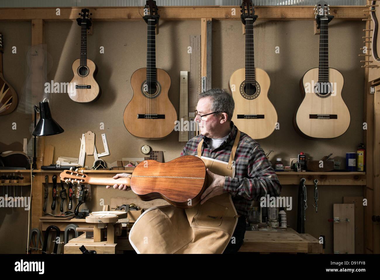 Liutaio finitura chitarra acustica in officina Immagini Stock