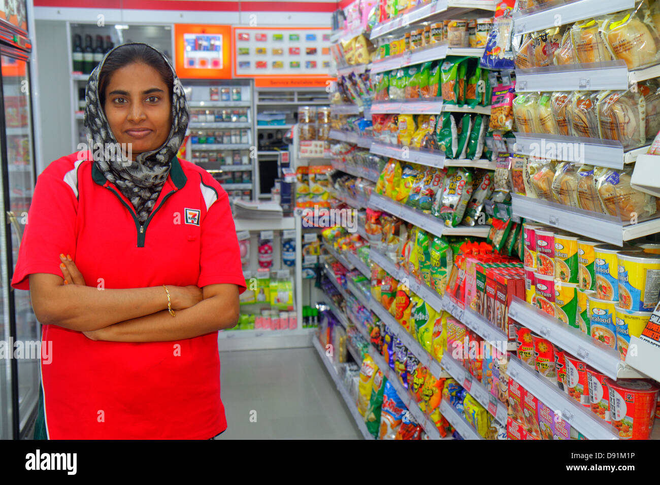 Singapore Kampong Glam Quartiere Musulmano Arab Street 7-Eleven convenience store business all'interno donna Immagini Stock