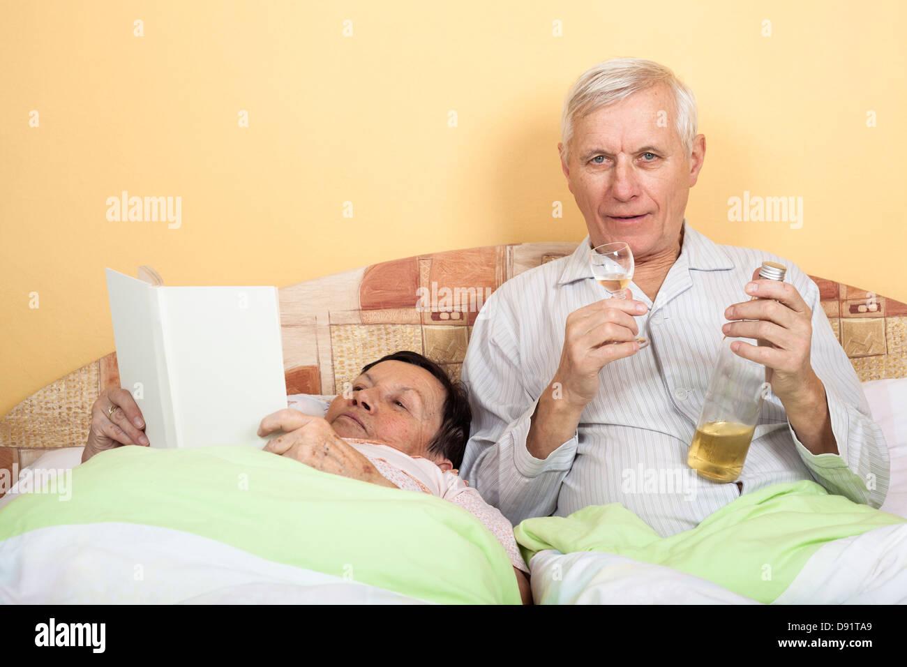 Coppia senior di riposo in letto con alcool e prenota Foto Stock