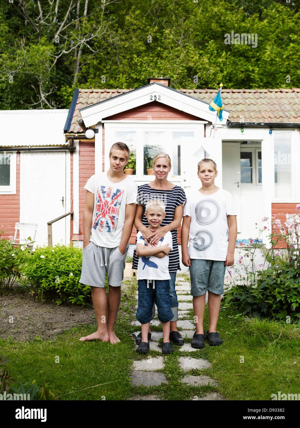 E madre di tre figli in piedi nella parte anteriore del weekend cottage Immagini Stock