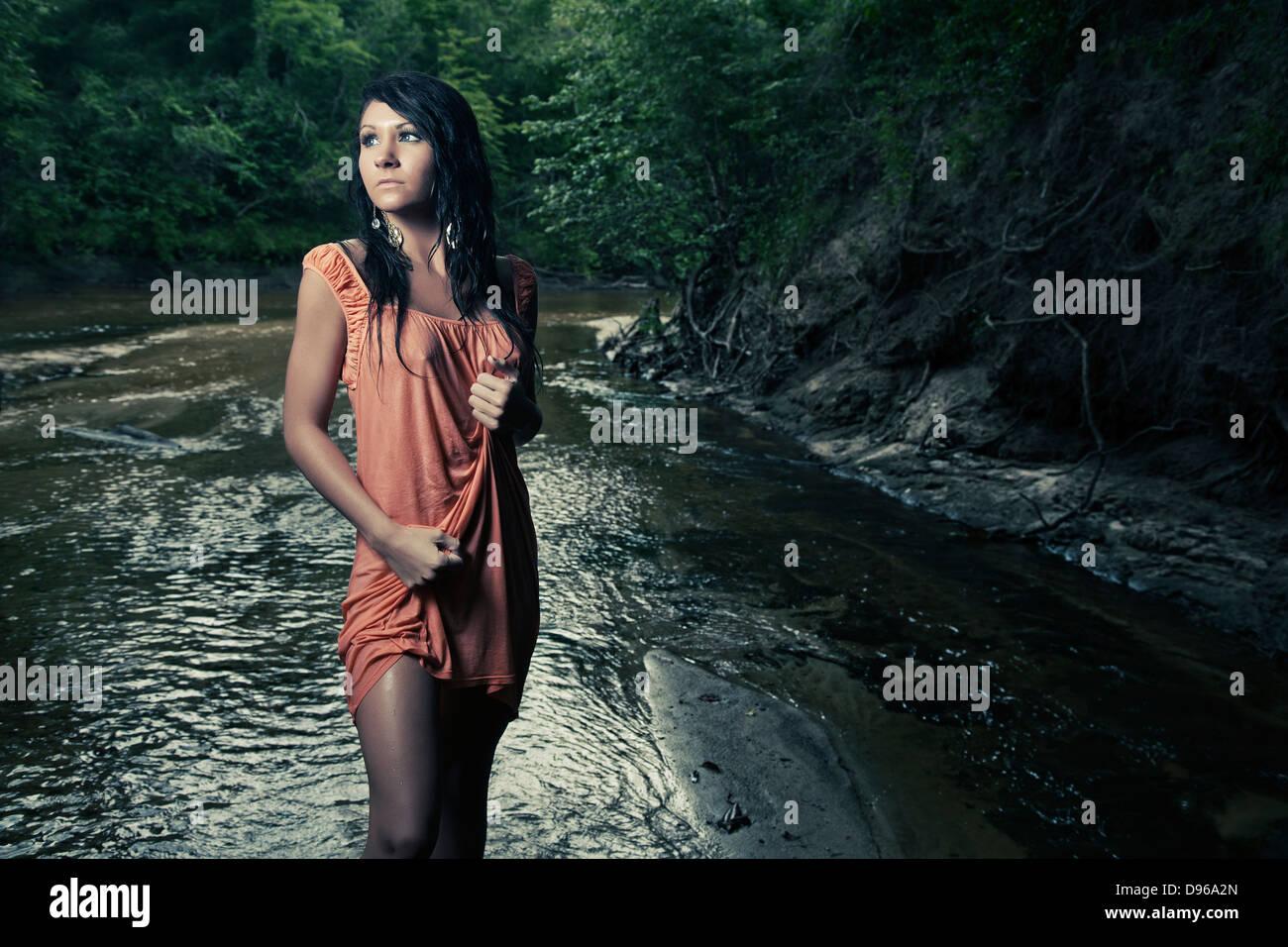 Donna in abiti bagnati in piedi in creek Immagini Stock