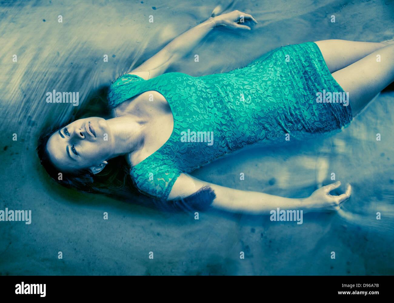 Donna in vestito blu galleggianti in acqua Immagini Stock