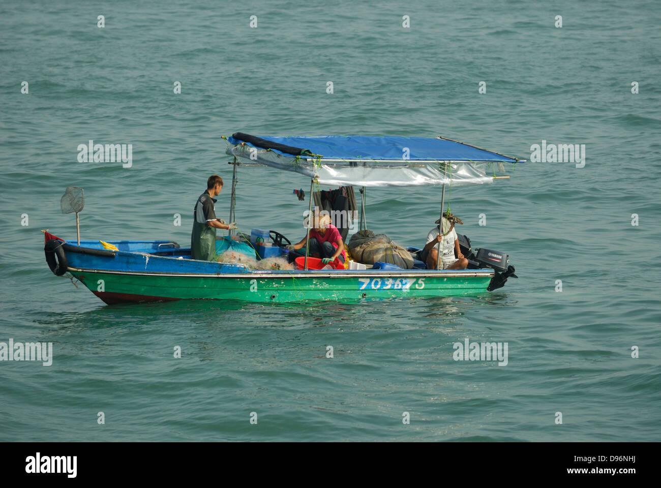 Fisherman e barca nel porto Victoria, Hong Kong Cina. Immagini Stock