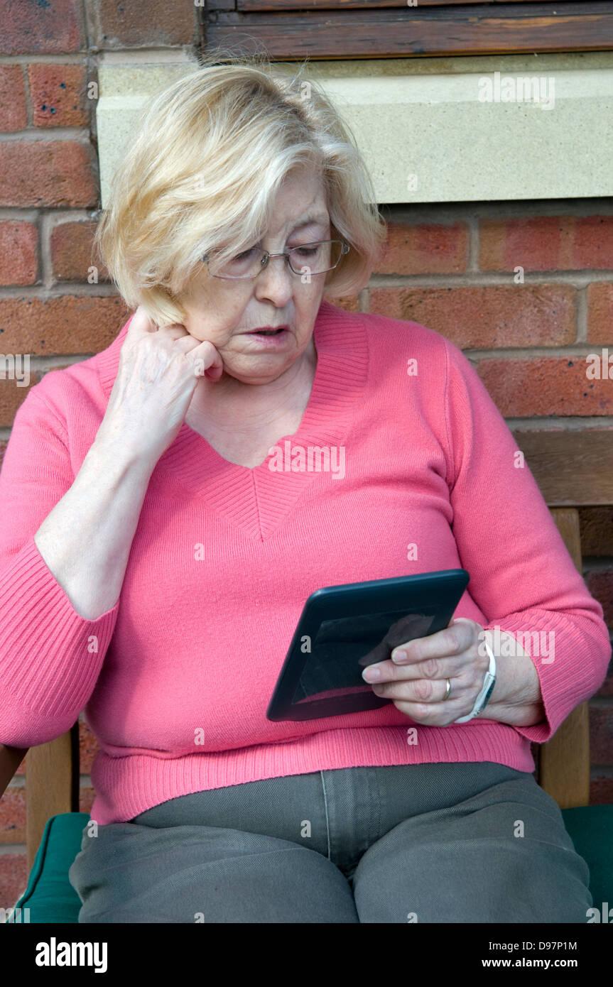 Senior signora lettura compressa in giardino Immagini Stock