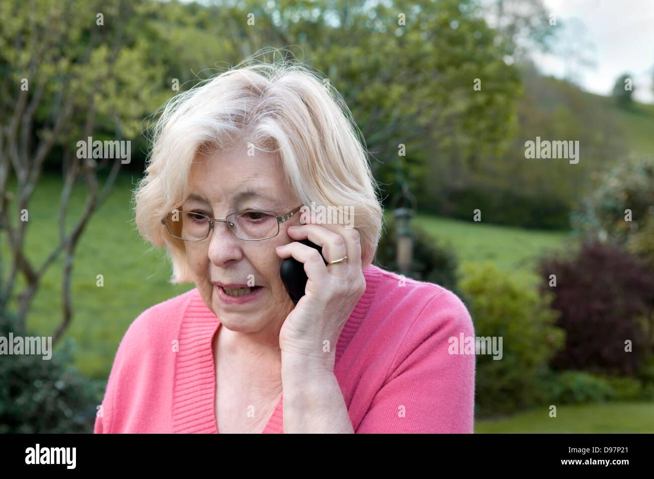 Senior lady tramite cellulare in giardino Immagini Stock