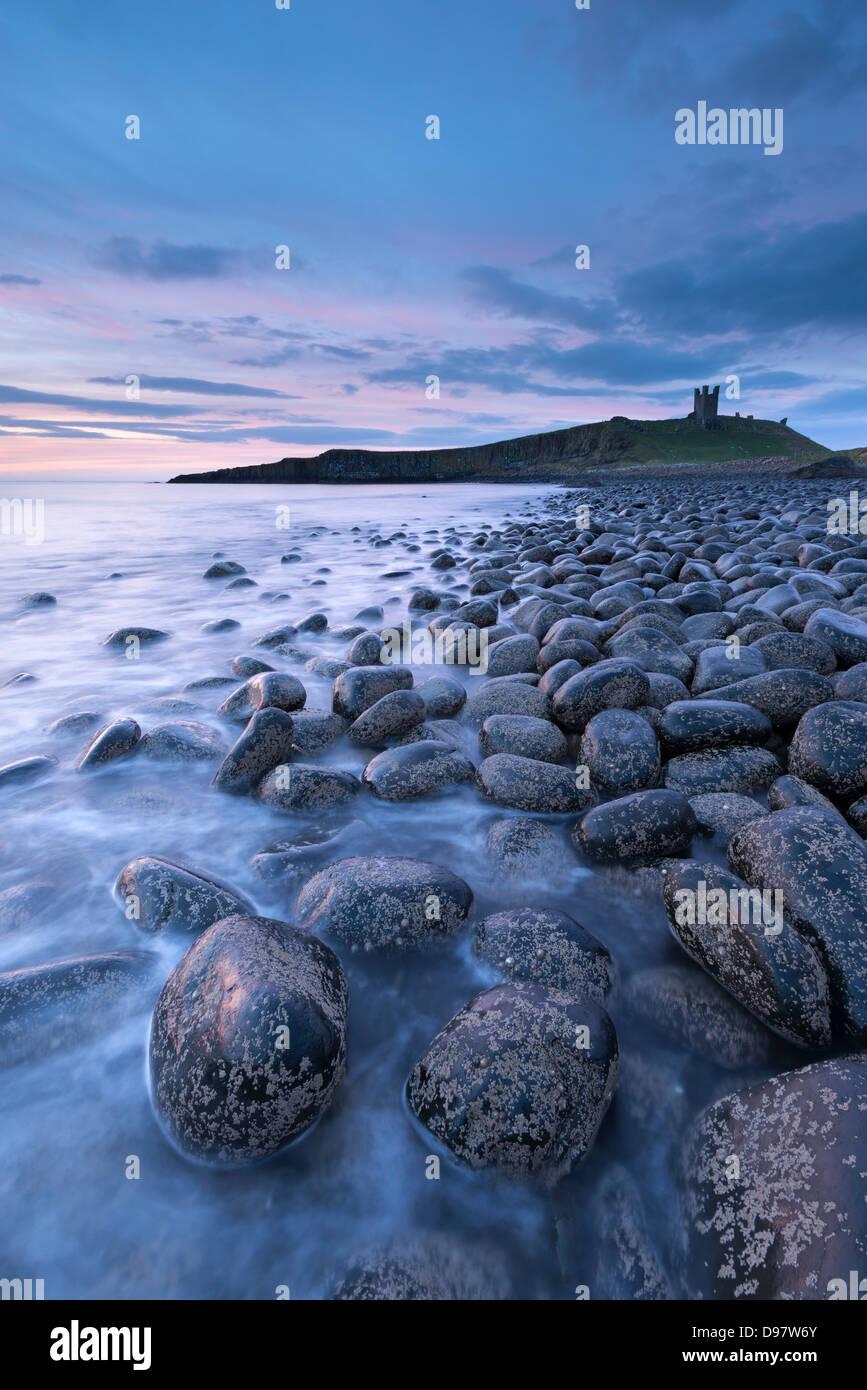 Il castello di Dunstanburgh all'alba di Embleton Bay, Northumberland, Inghilterra. Molla (maggio) 2013. Immagini Stock