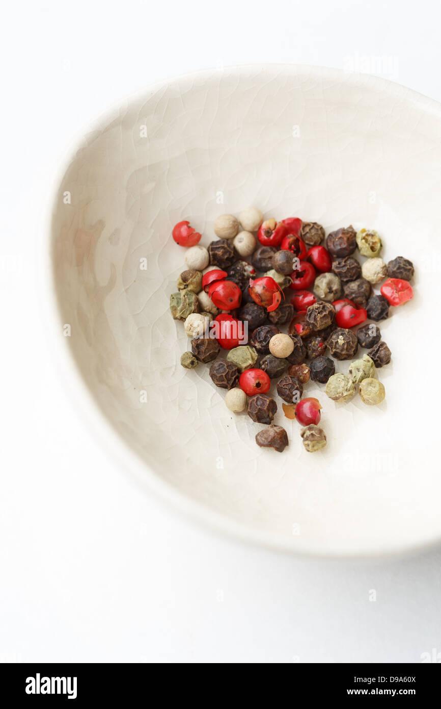 Ciotola bianco con varietà di grano di pepe Immagini Stock