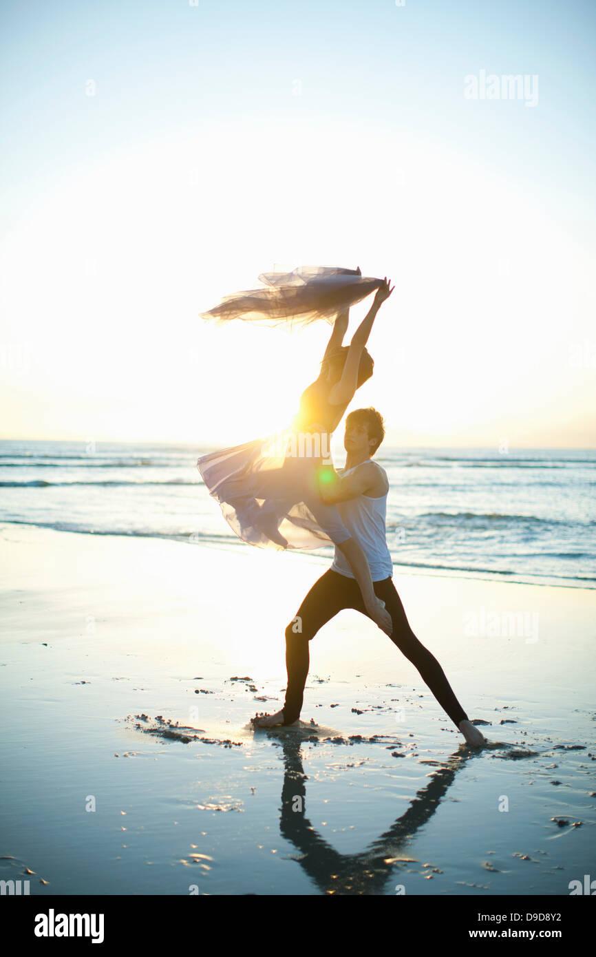 Giovane uomo sollevamento partner di ballo sulla spiaggia soleggiata Immagini Stock