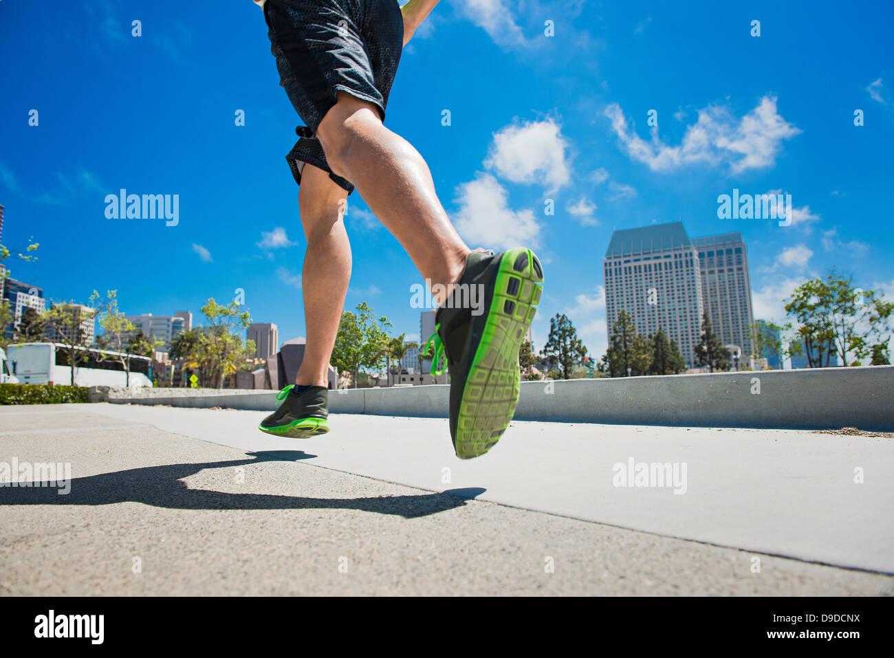Giovane uomo jogging in città, sezione bassa Immagini Stock