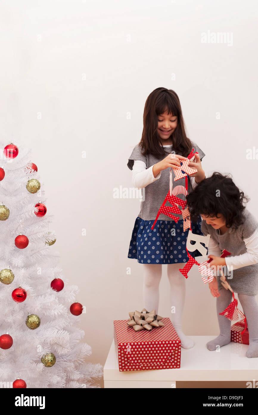 Due ragazze la preparazione per il Natale, mettendo un banner di Natale Immagini Stock