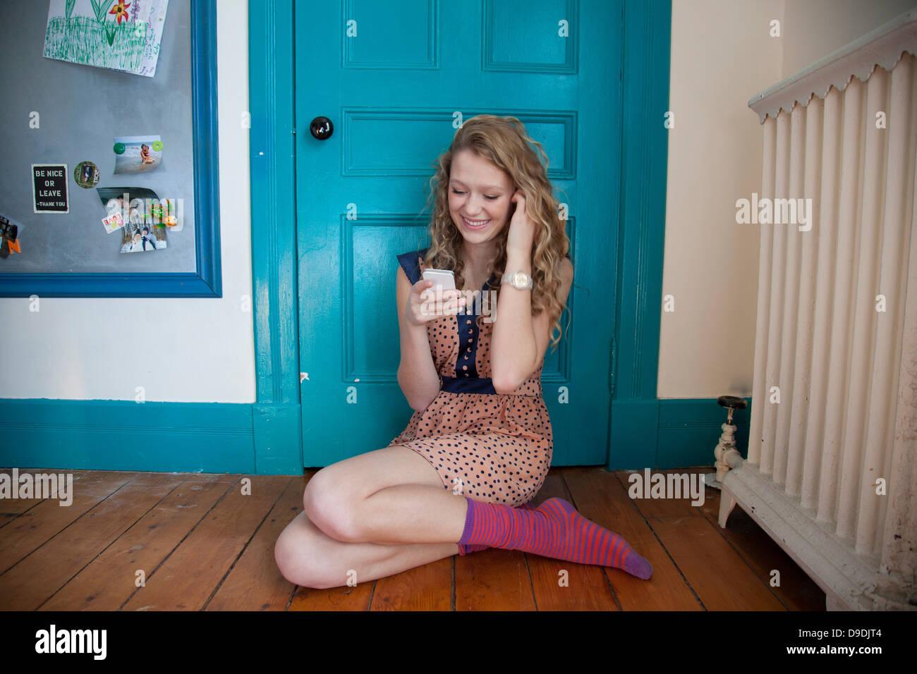 Ragazzo seduto di fronte blu porta, tramite telefono mobile Immagini Stock