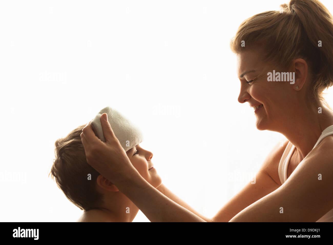 Madre usando il panno per raffreddare il figlio verso il basso Immagini Stock