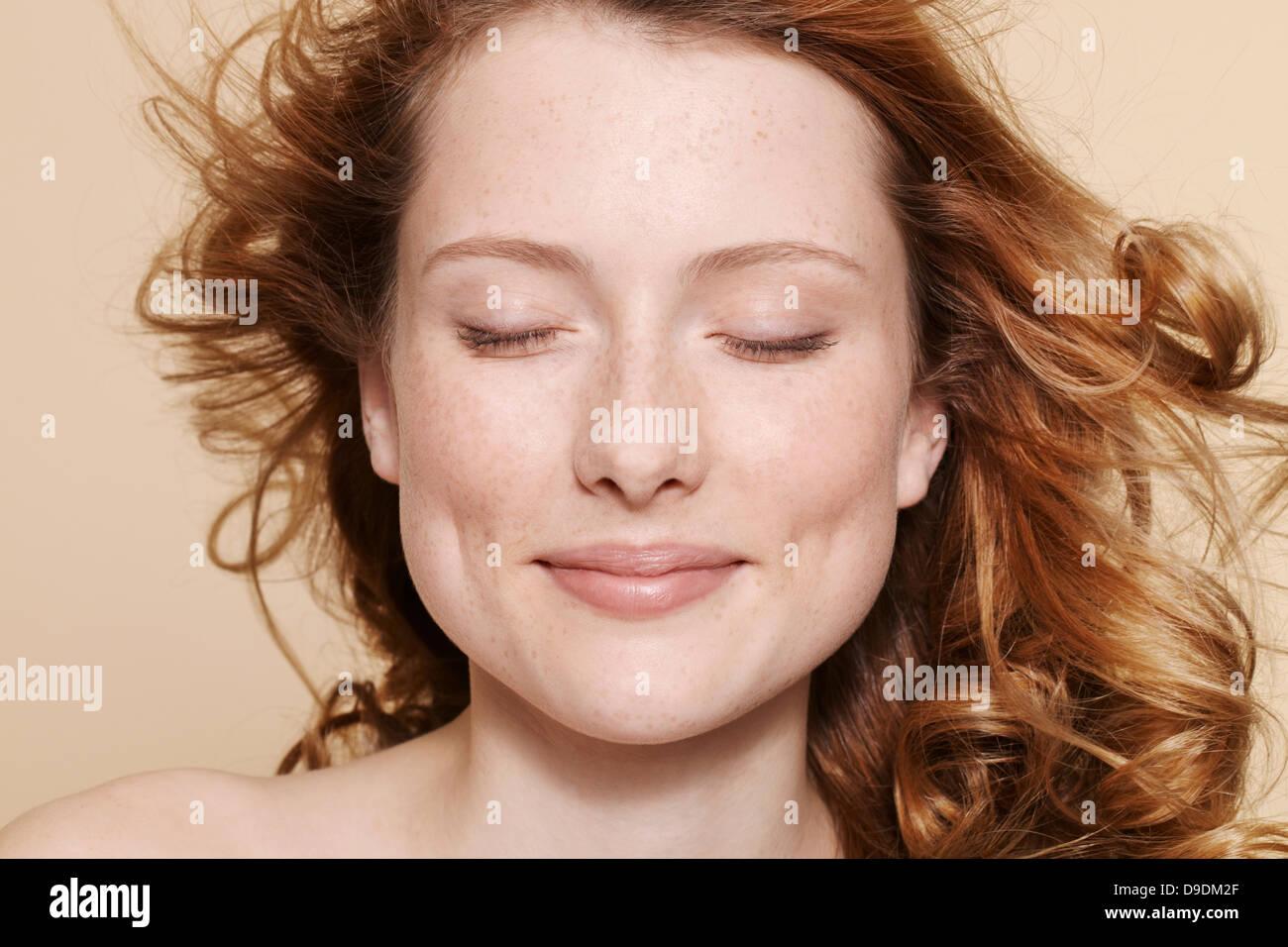 Studio shot della giovane donna con ricci capelli rossi a occhi chiusi Immagini Stock