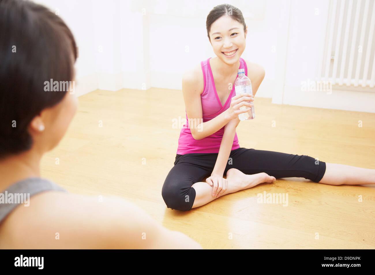 Donna seduta sul pavimento con una bottiglia d'acqua Immagini Stock