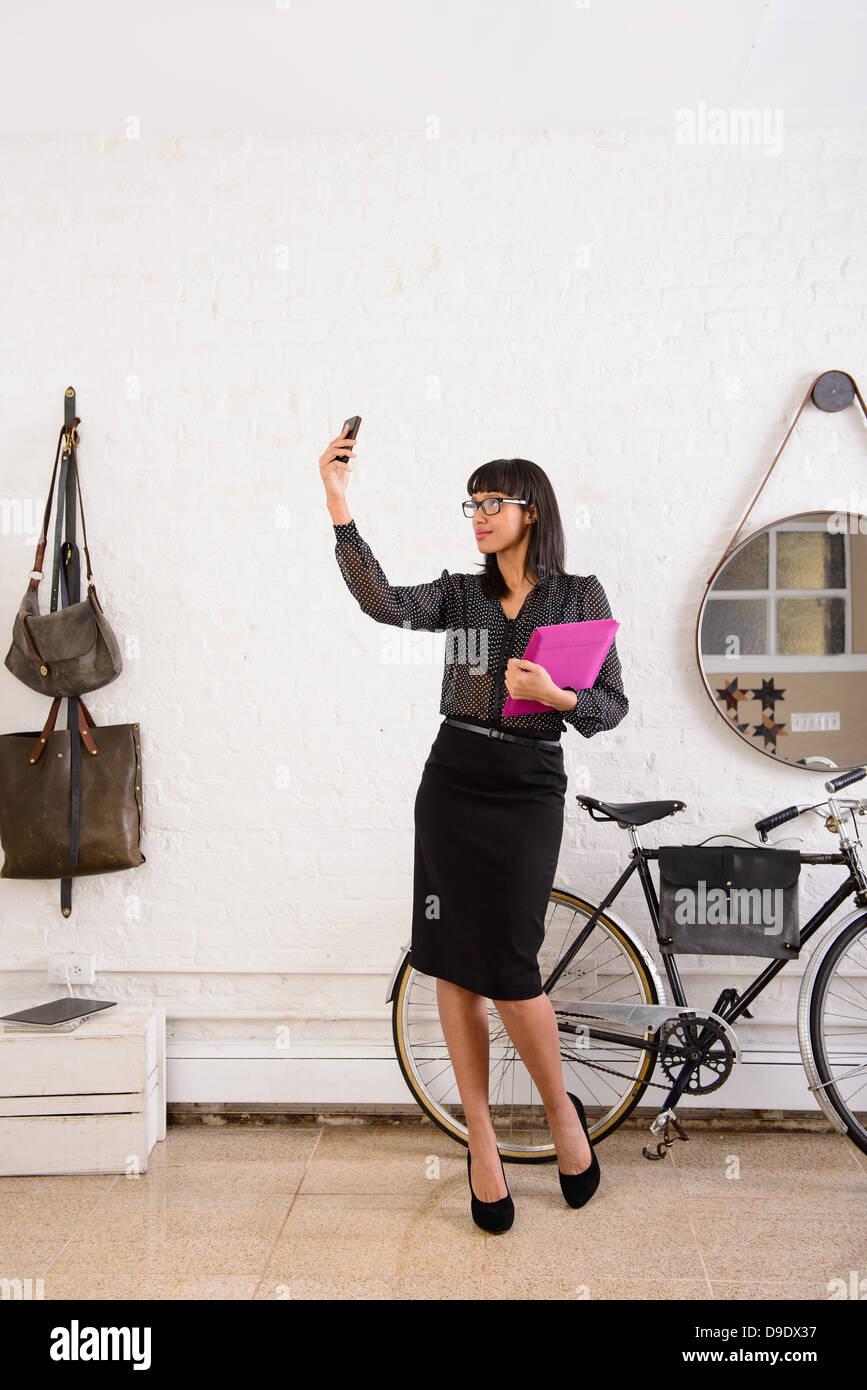 Donna di scattare una foto di se stessa con lo smartphone Immagini Stock