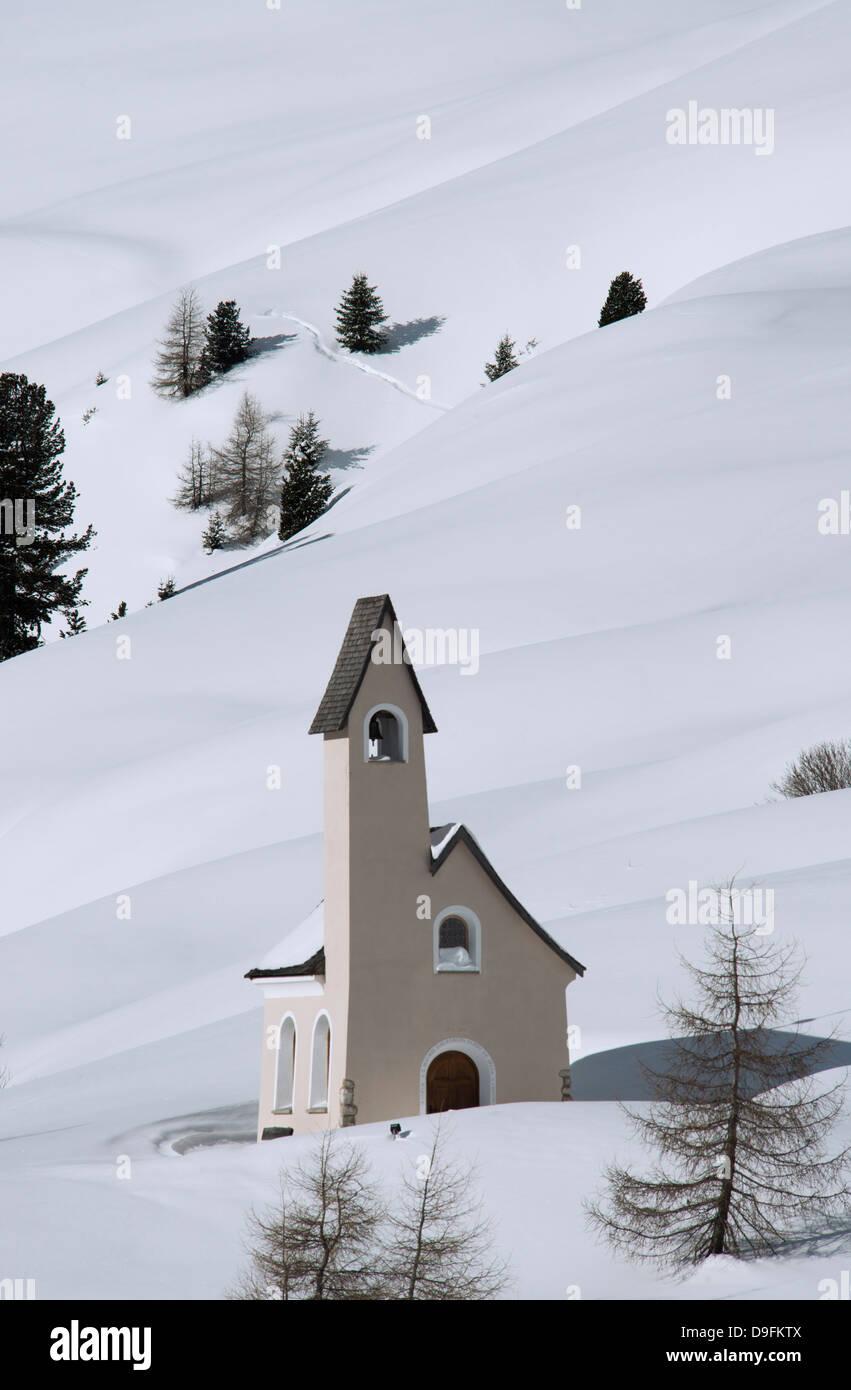 Uno stile moderno cappella su una coperta di neve hillside al Passo Sella nelle Dolomiti, Alto Adige, Italia Immagini Stock