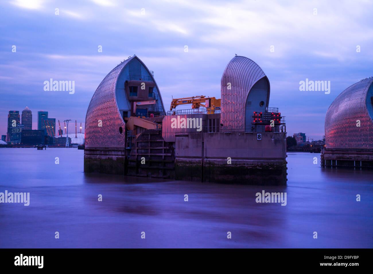 La sezione del fiume Thames Flood Barrier al crepuscolo con Canary Wharf e l'Arena O2 in background, London, Immagini Stock