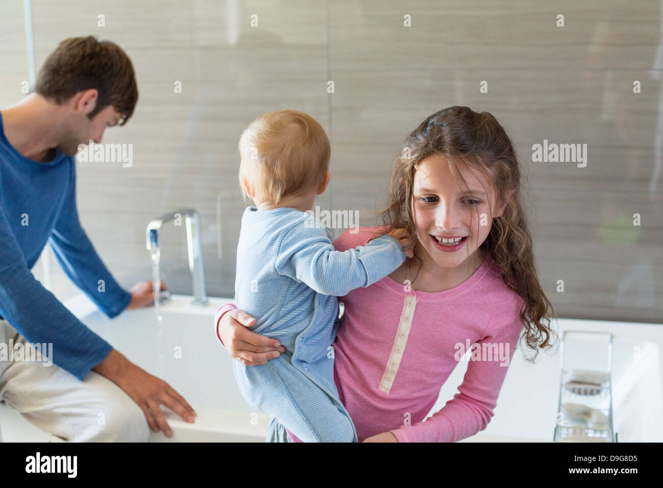 Ragazza sorridente con suo fratello e suo padre seduto su un bordo vasca nella stanza da bagno Immagini Stock
