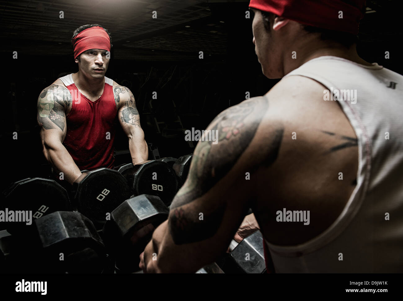 Muscolare di giovane uomo cercando in palestra specchio Immagini Stock