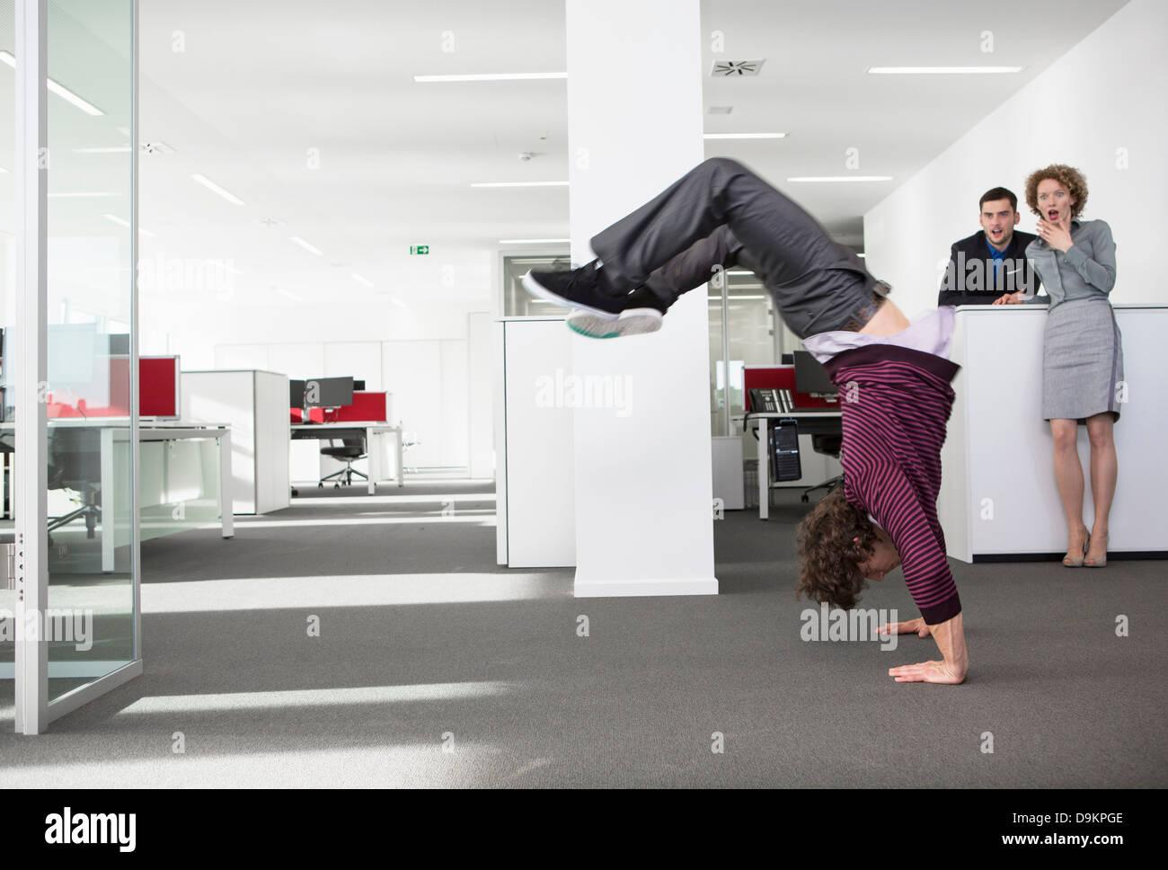 Lavoratore di ufficio facendo handstand, colleghi guardando in stato di shock Immagini Stock