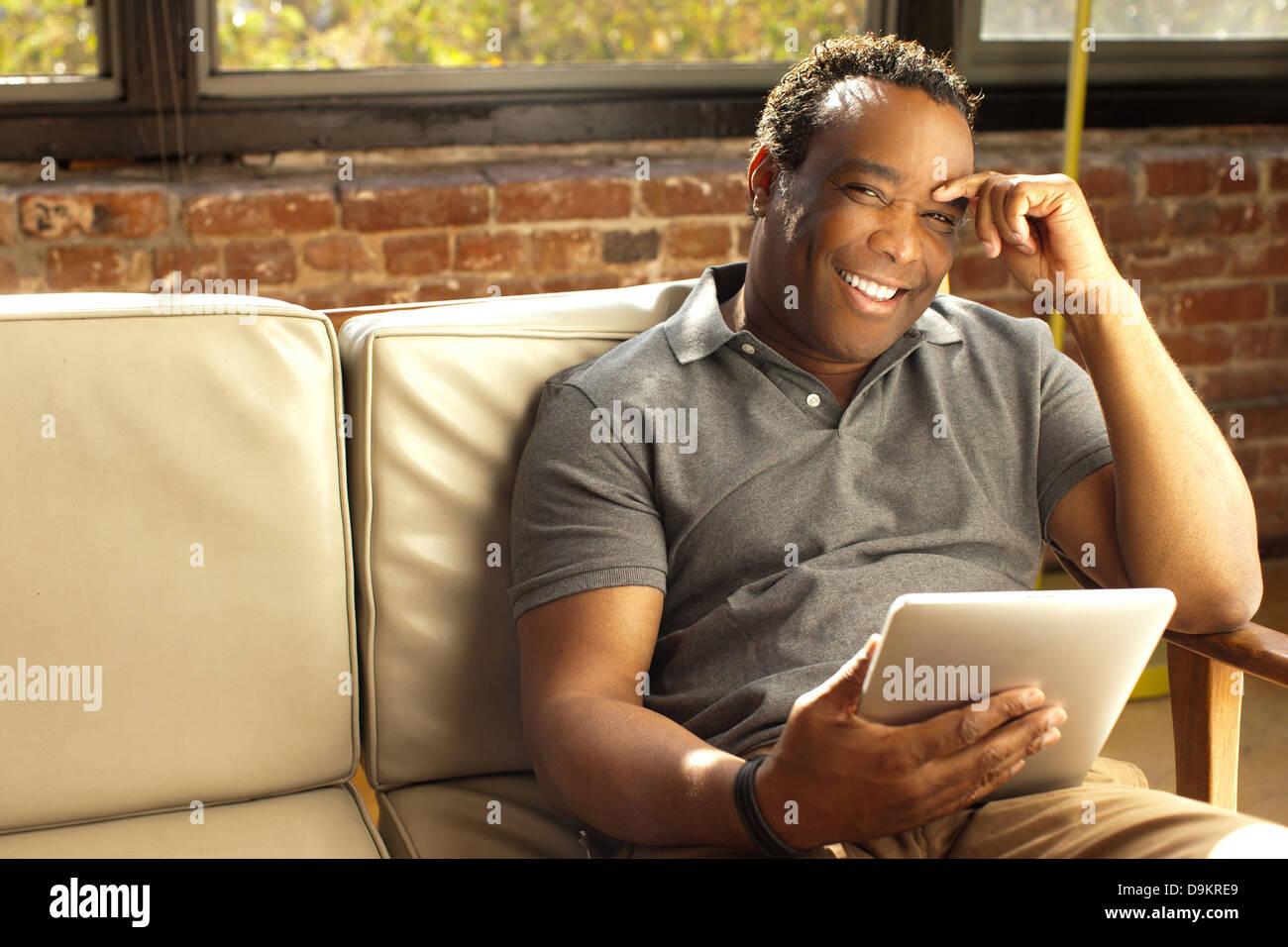Uomo in posa con sorriso carismatico holding tavoletta digitale Immagini Stock