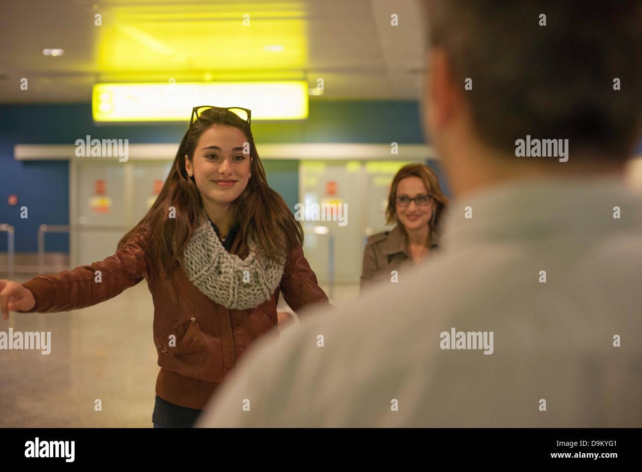 Ragazza adolescente di arrivare in aeroporto, uomo in primo piano Immagini Stock
