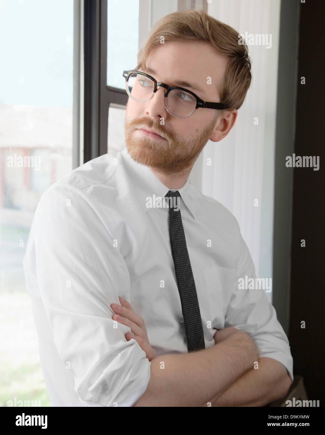 Giovane uomo che indossa gli occhiali e cravatta che guarda lontano Foto Stock