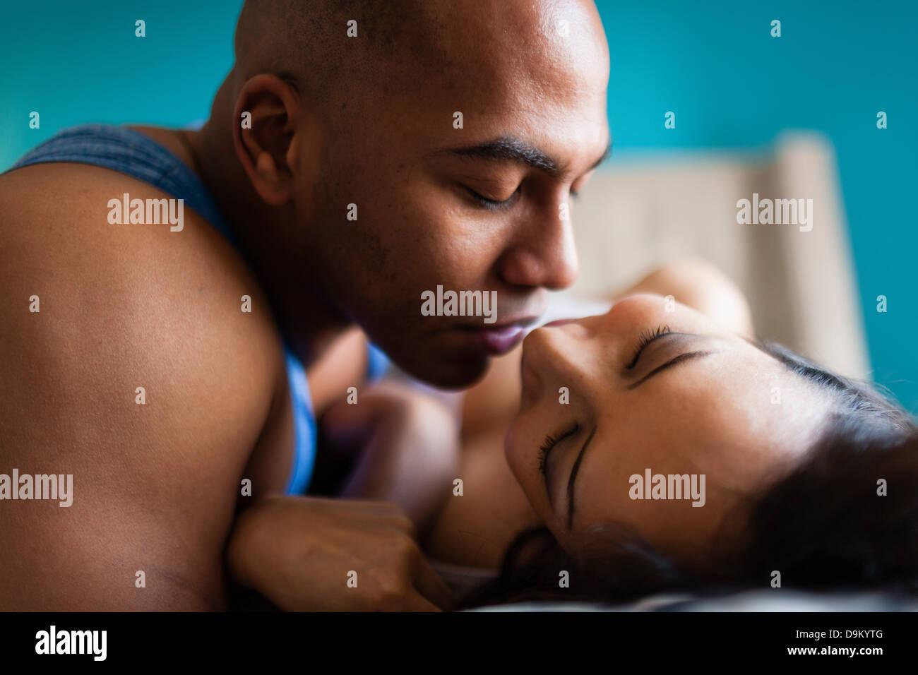 Metà adulto giovane kissing sul letto Immagini Stock