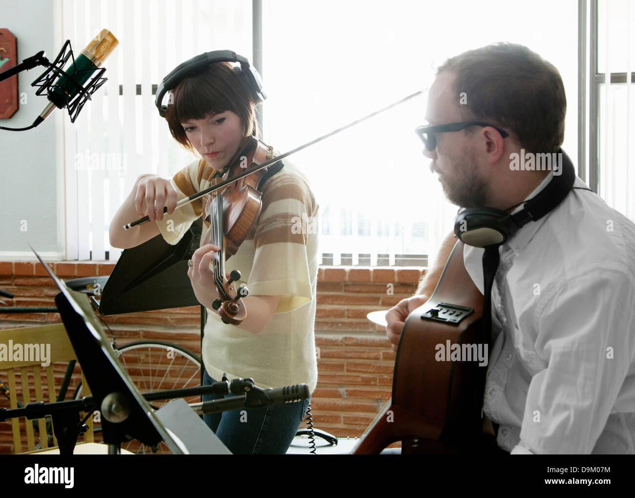 Giovane uomo e donna suona il violino e chitarra in sala musica prove generali Immagini Stock