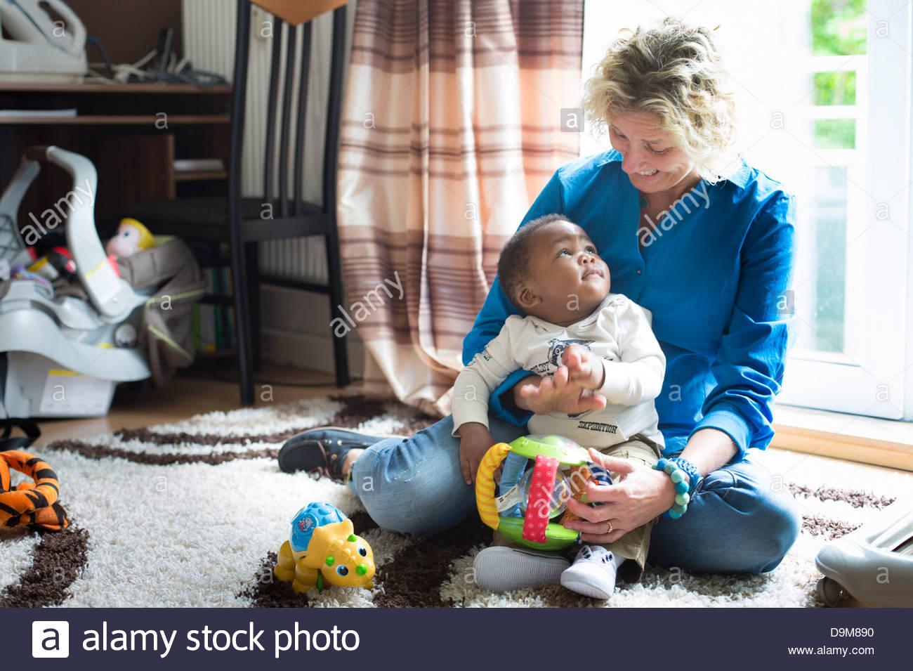 Donna che gioca con la sua adozione baby boy Immagini Stock