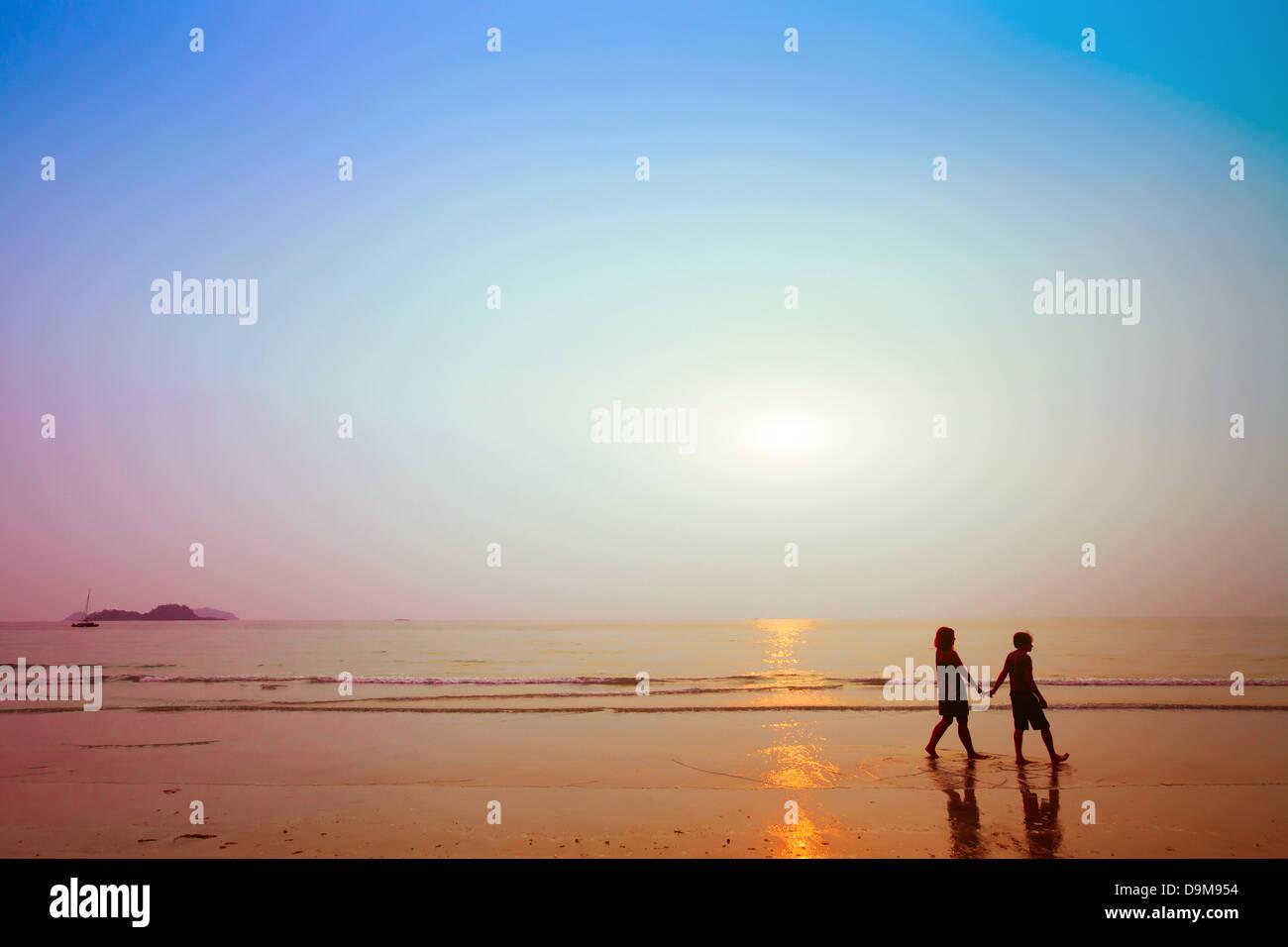 Sagome di coppia sulla spiaggia al tramonto Immagini Stock