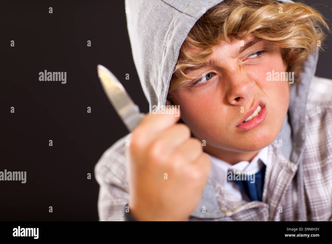 Violento teen boy tenendo un coltello su sfondo nero Immagini Stock