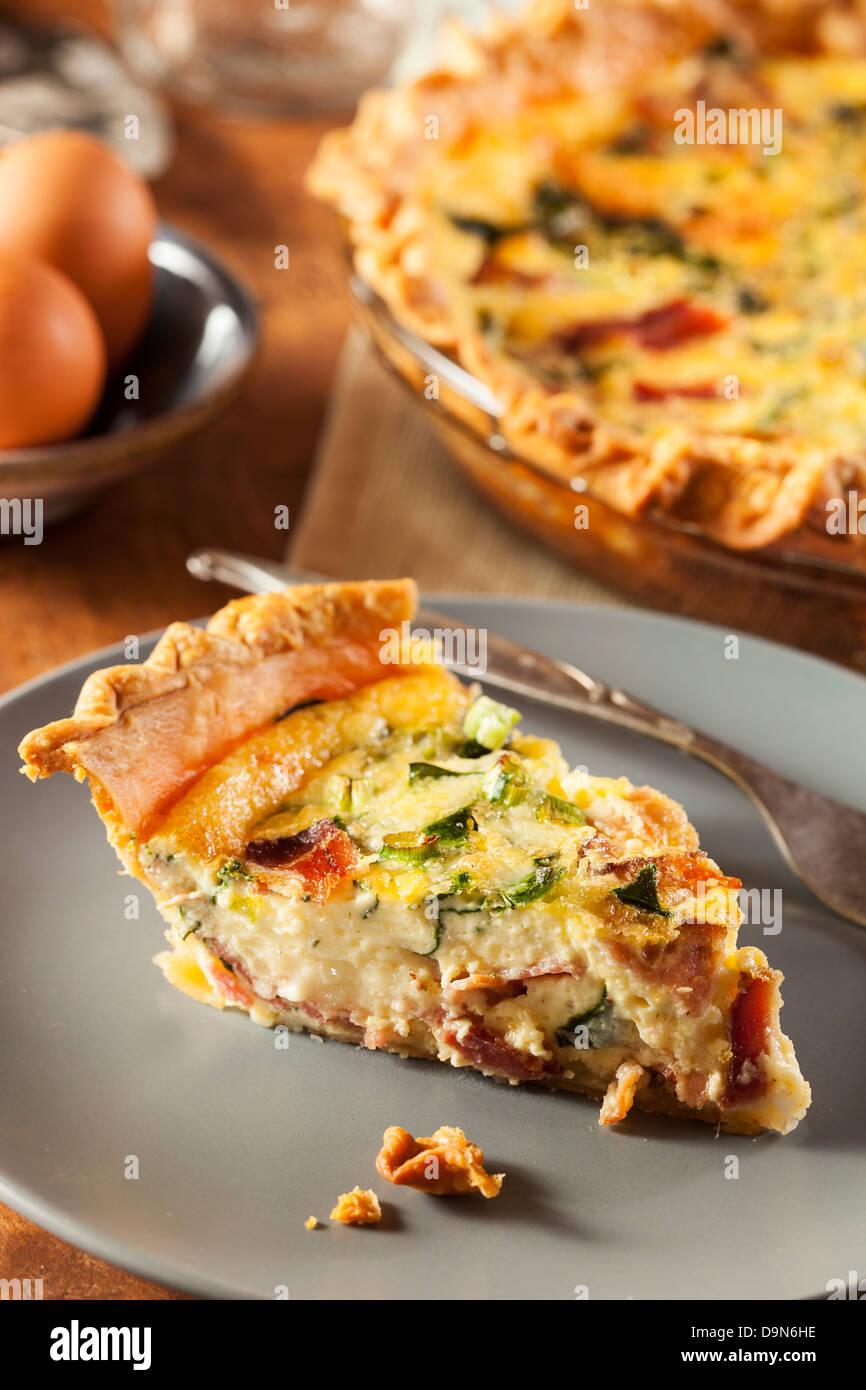 In casa di spinaci e pancetta Quiche alle uova in una base di pastafrolla per torta Immagini Stock