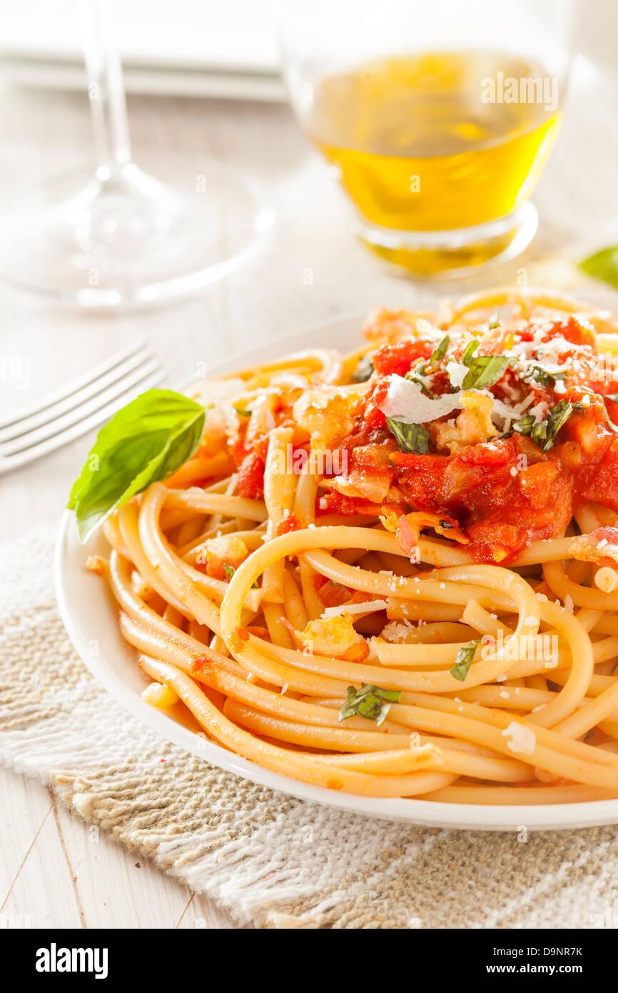 In casa Bucatini all'Amatriciana la pasta con il sugo di pomodoro e basilico Immagini Stock