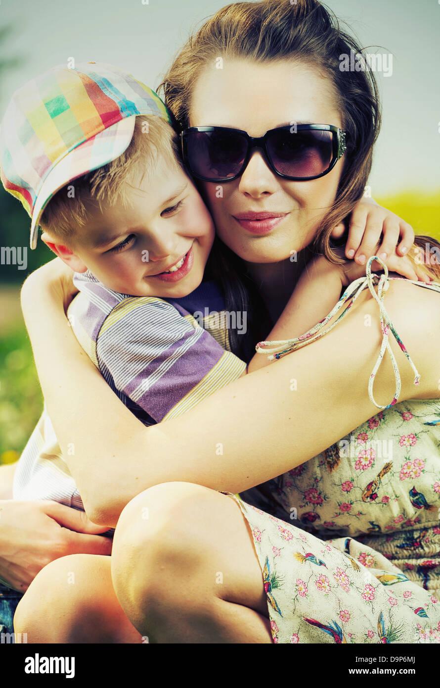 Bella la mamma che abbraccia il suo grazioso piccolo figlio Immagini Stock
