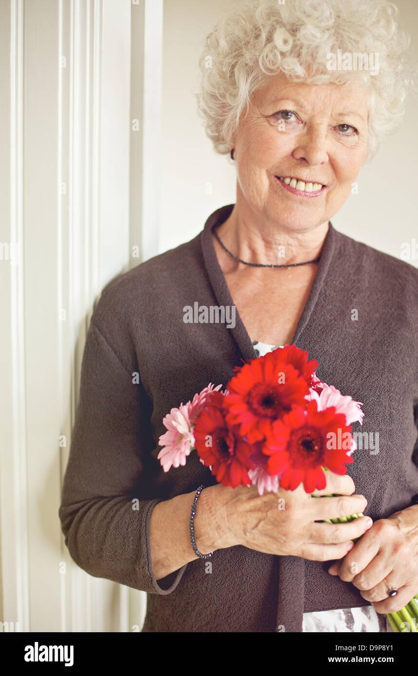 Felice donna senior tenendo un bouquet di fiori freschi Immagini Stock