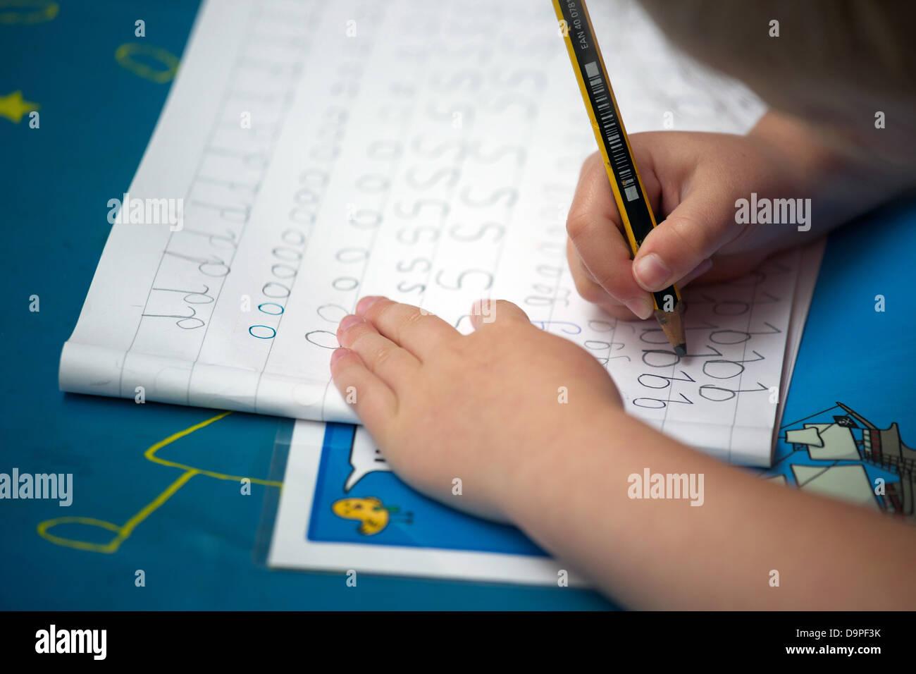 Close up di un Regno Unito la scuola primaria bambino facendo pratica della scrittura. Immagini Stock