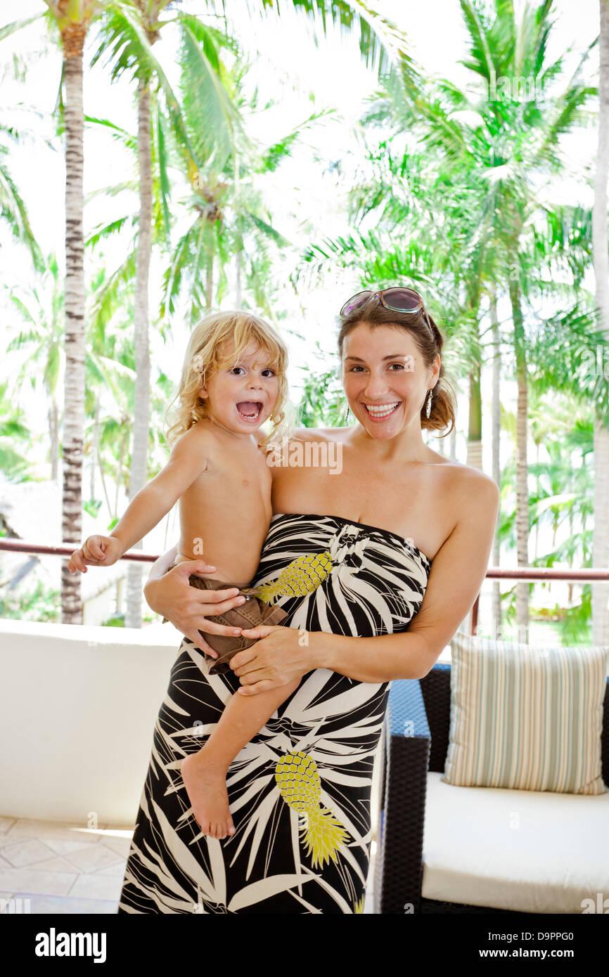 Donna elegante con il bambino in prossimità di alberi di palma Foto Stock