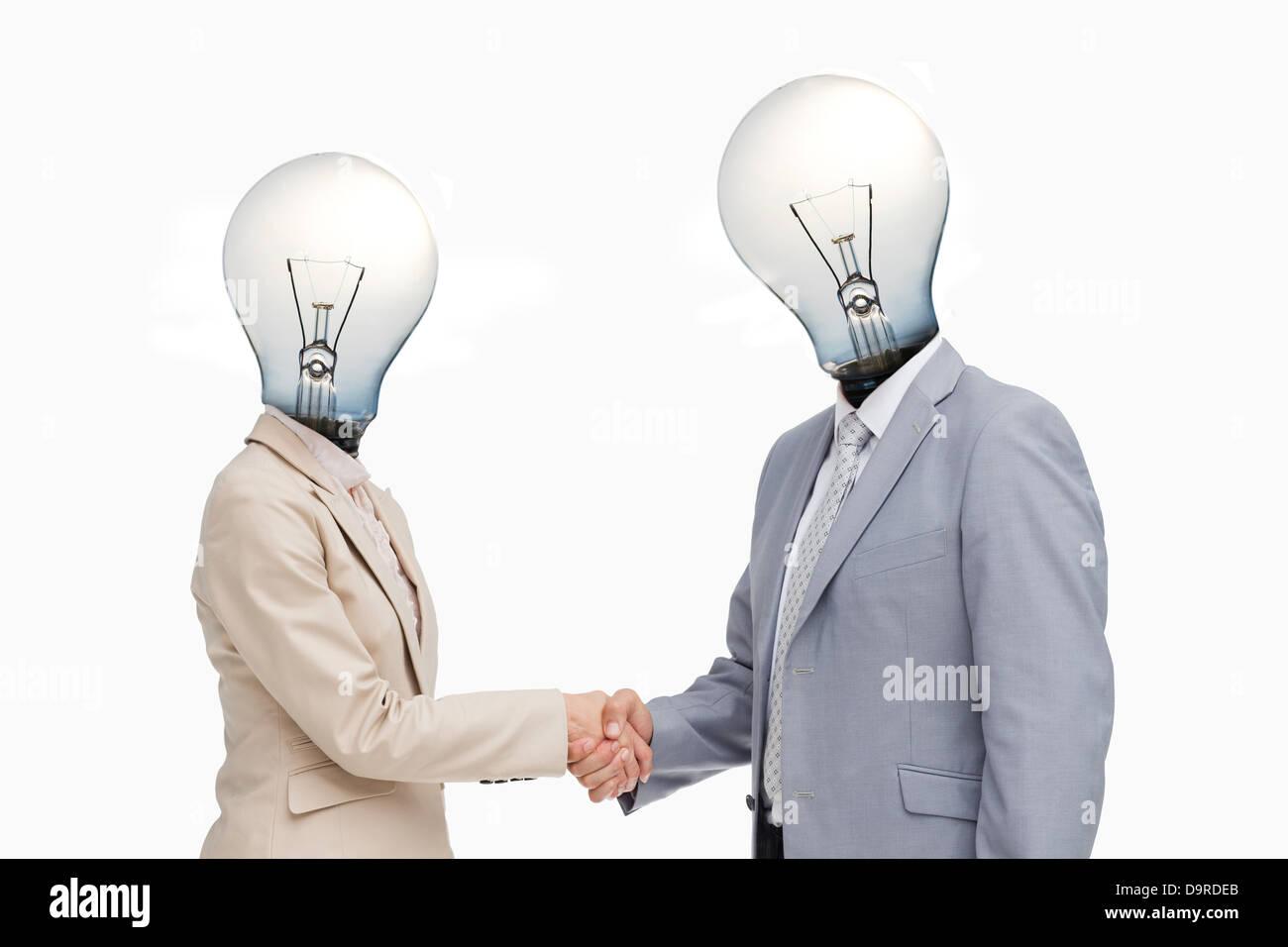 La gente di affari con teste di lampadine saluto con una stretta di mano Immagini Stock