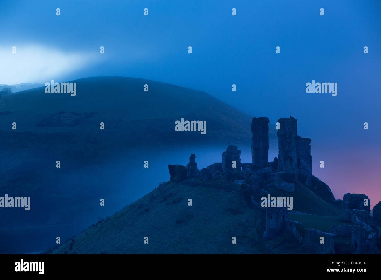 Corfe Castle nella nebbia all'alba, Dorset, England, Regno Unito Immagini Stock