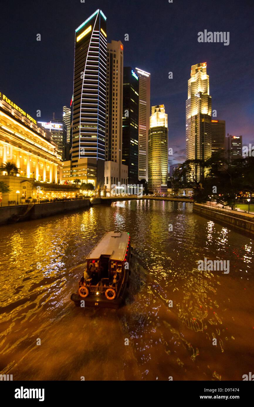 Il Cavenagh Bridge, una barca sul fiume Singapore, il Fullerton Hotel e il quartiere centrale degli affari di notte, Immagini Stock