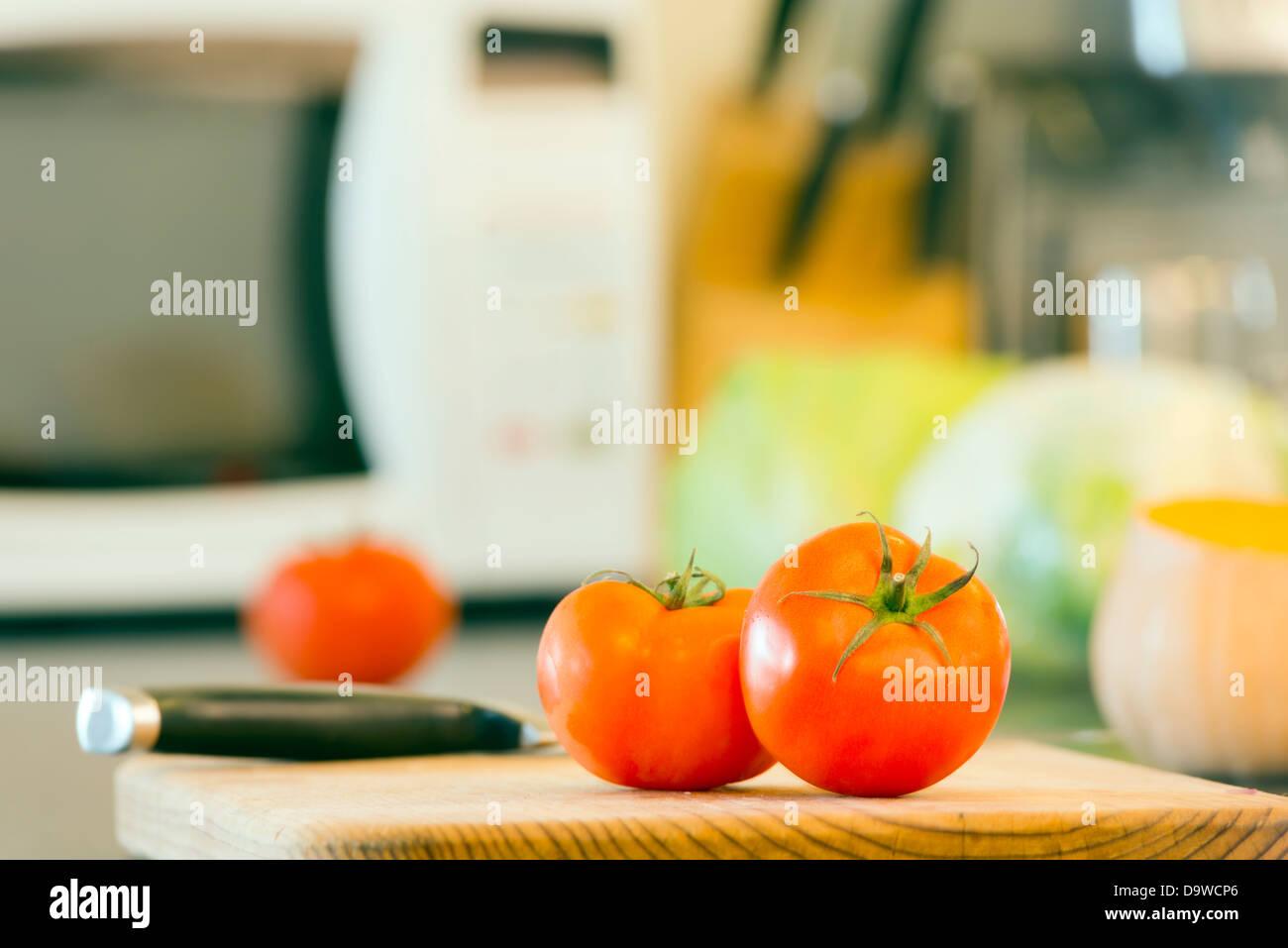 La preparazione di cibi freschi sul banco di cucina, con pomodori, zucca e altri ortaggi in background Immagini Stock