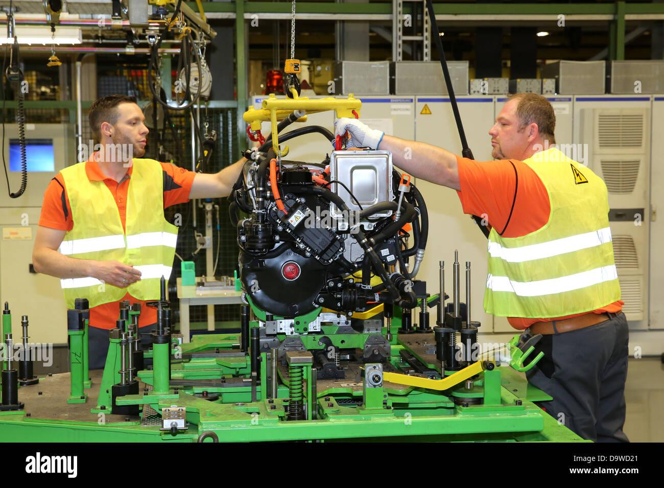 Gli operatori si spostano di un motore elettrico in posizione per il montaggio in una Ford FocusElectric auto presso Immagini Stock