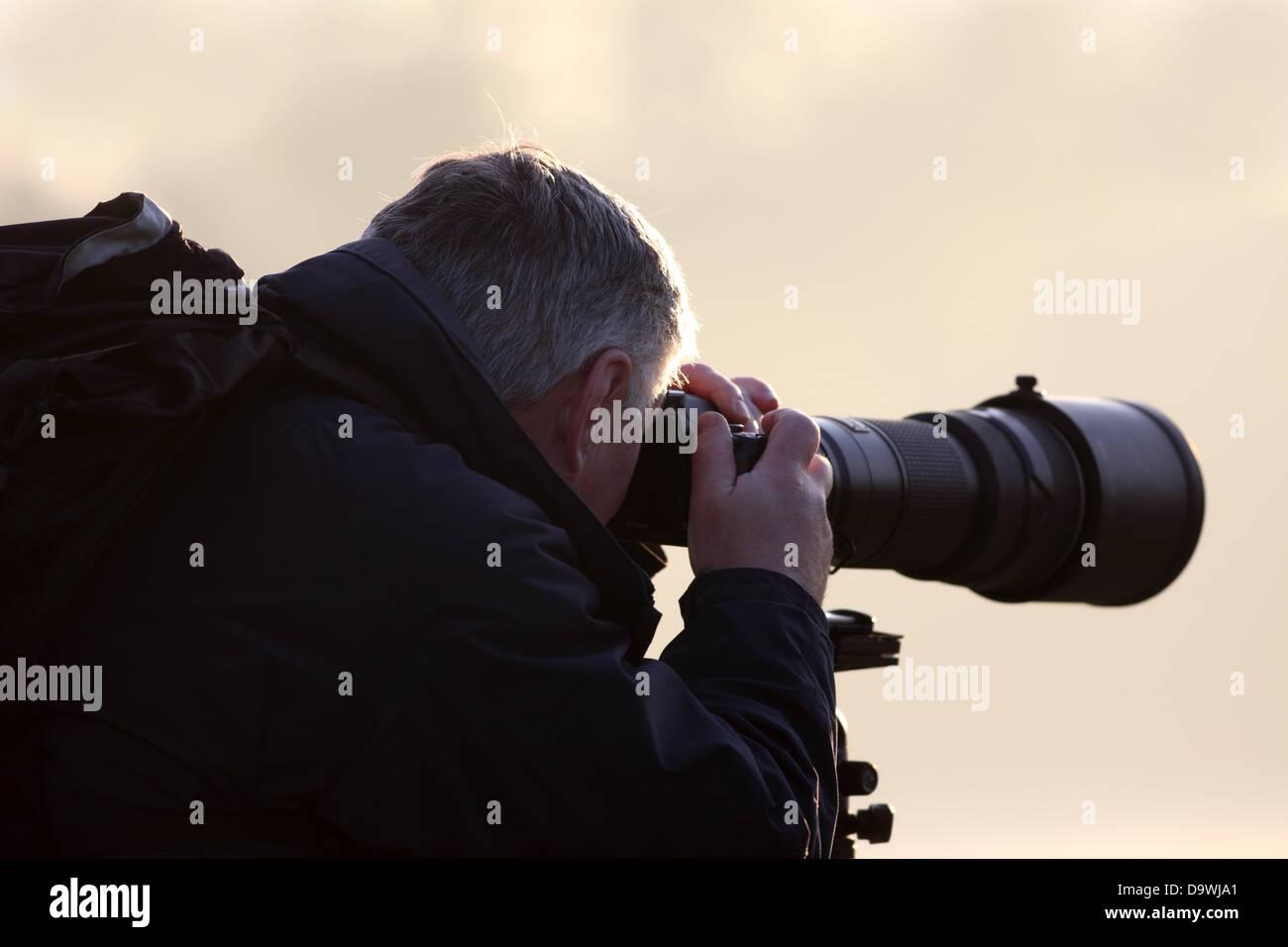 Fotografo con un teleobiettivo Immagini Stock