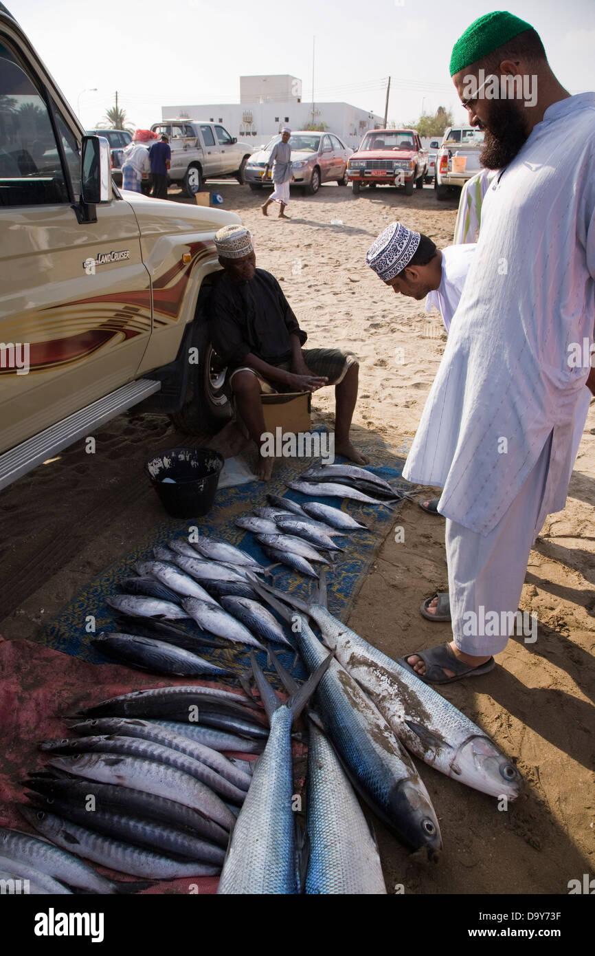 I pescatori di vendere le loro catture di fresco da spiaggia sul Golfo di Oman in il Parka distretto di Mascate Immagini Stock