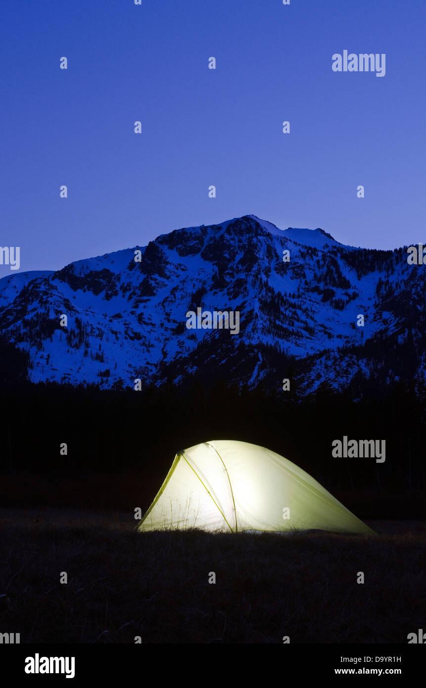 Una tenda è illuminato al crepuscolo sotto il monte Tallac in Lake Tahoe, CA. Immagini Stock