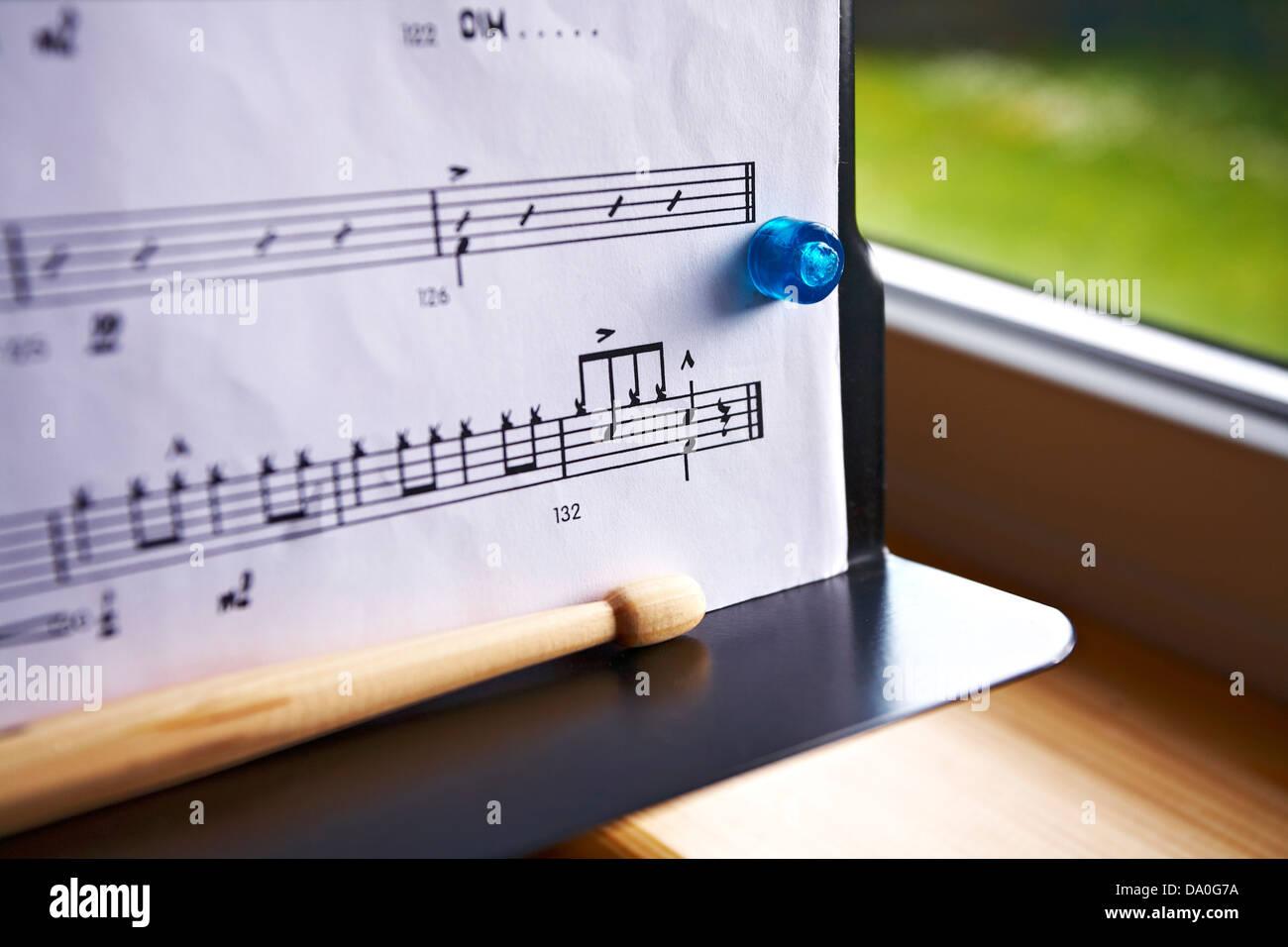 Tamburo musica notazione punteggio mostra gli accenti su music stand. Musica tenuto in posizione con magnete blu. Immagini Stock