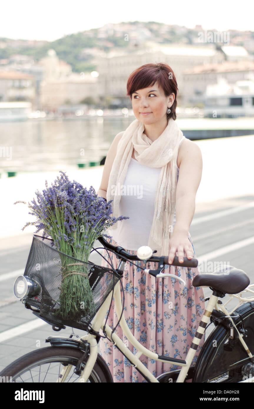 Donne azienda retrò bike con fiori di lavanda in basket Immagini Stock